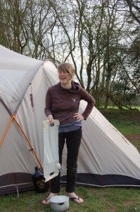 cath beside tent and camping with water bag