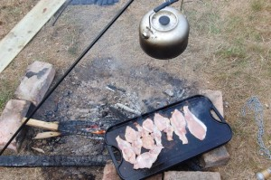 Bacon cooking on a campfire at Dernwood Farm campsite in East Sussex