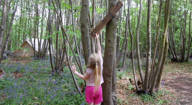 Adjusting a sign in the woods at Welsummer campsite