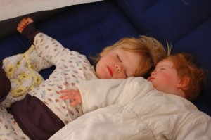 Two babies in pyjamas and wearable sleeping bag camping