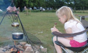 Girl with a hot chocolate dipper treat sitting around the campfire