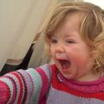 A toddler shouting No